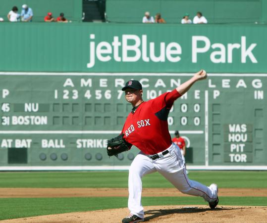 The scoreboard is truly a blank slate, as Red Sox pitcher Jon Lester warms up before the first exhibition game ever at JetBlue Park, against Northeastern.