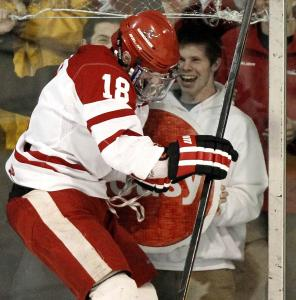 Hingham sophomore Sam D&#8217;Antuono smashes a little glass after his third goal gave the Harbormen an OT victory.