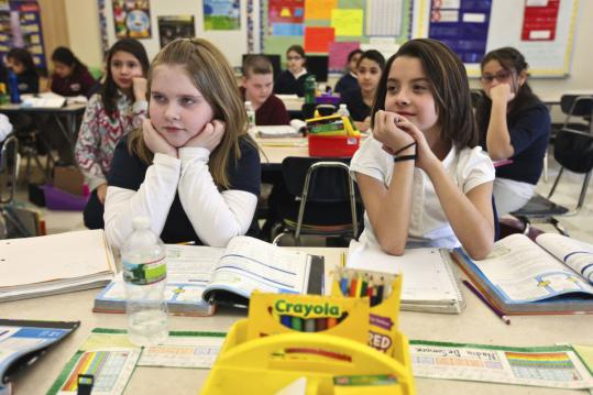 Delaney Cesareo, 10, (left) and Nadia DeSimone, 11, pay attention to the lesson at the Paul Revere Elementary School in Revere.