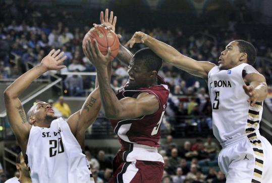 Sean Carter of UMass attempts to navigate the defense of St. Bonaventure's Da'Quan Cook (20) and Jordan Gathers (5) during the Bonnies' A-10 semifinal win.