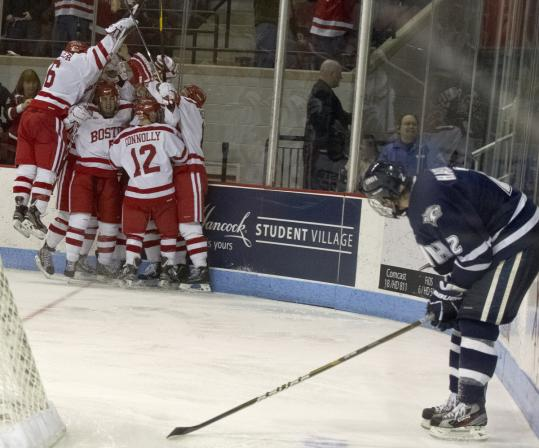 New Hampshire's Connor Hardowa steals a quick glance as the celebration among Boston University players gets started . . .