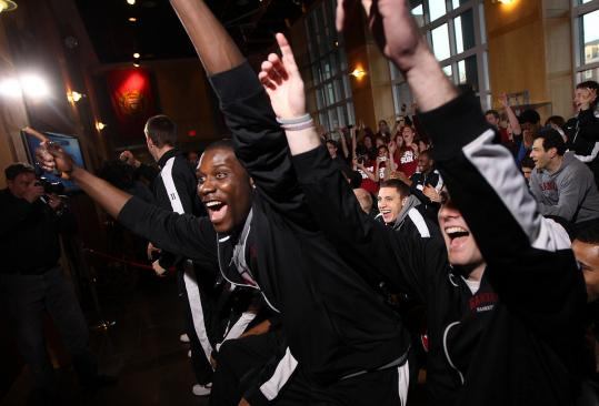 Forward Kyle Casey (center) leaps from his seat after Harvard's name was called as the No. 12 seed in the East Regional.