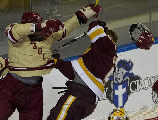 BC's Bill Arnold checks Minnesota-Duluth's Chris Casto's helmet off in first-period action.