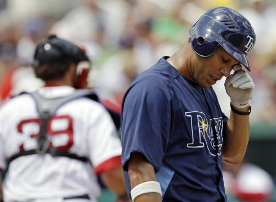 Rays first baseman Carlos Pena heads to the dugout, one of Josh Beckett&#8217;s five strikeout victims.
