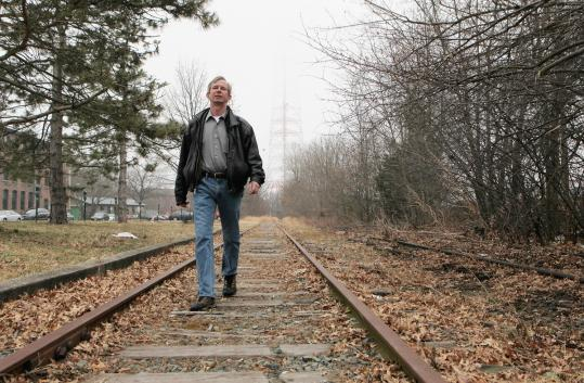 Newton resident Jerry Reilly (left) explores an unused rail bed that eventually may resemble a popular trail (right) in Milford.