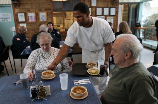 Northeast Correctional Center inmate Calvin Hodge serves lunch to Jacqueline Friedman and Walt Tetschner at the Concord facility's public restaurant, the Fife and Drum.
