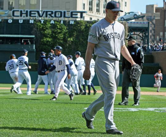 Alfredo Aceves walked off after surrendering the winning hit as the Tigers celebrated behind him. Coverage, C1.