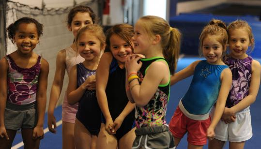 Young gymnasts take a break at the Melrose Family YMCA. More than 100 girls are on teams that compete in league championships.