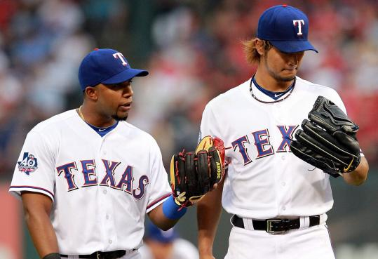 Elvis Andrus (left) tries to calm Yu Darvish during his rough debut for the Rangers in which Seattle tagged him for four first-inning runs.