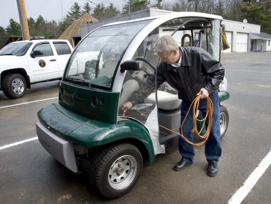 Tyngsborough Selectman Allen Curseaden unravels an extension cord at one of the town's new charging stations to plug in his used Ford Th!nk.