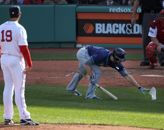 Luke Scott, who considers Fenway Park an uncomfortable relic, retrieves a piece of paper in front of Josh Beckett.