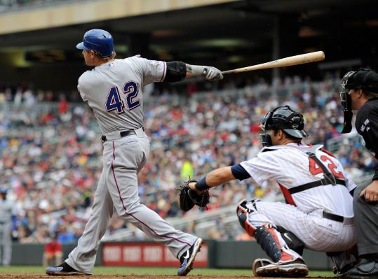 Josh Hamilton follows through on his two-run homer in the eighth inning at Target Field.