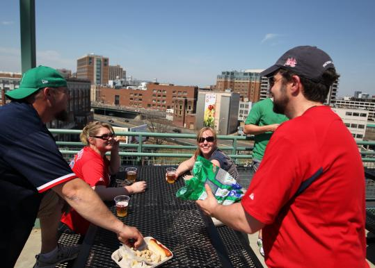 Brian Gannon offered peanuts at the upper left field corner of Fenway Park, where he and other fans could see the Boston Marathon. He has been coming to Patriots Day games for a decade to watch the two sports.