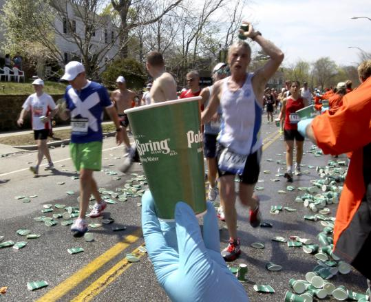 Spectators offered runners cups of water along Commonwealth Avenue during the Boston Marathon.