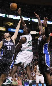Brandon Bass hits a hook shot over Magic defenders Ryan Anderson (left) and Glen Davis in the first quarter.