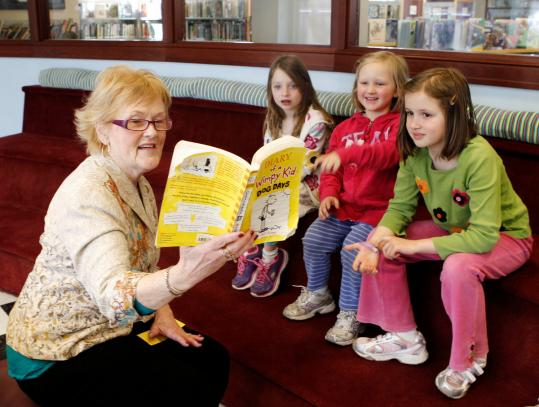 "Nancy Smith read ""Diary of a Wimpy Kid' to Sydney Clausen and Tessa and Thea Manderson recently at the Newburyport Public Library."