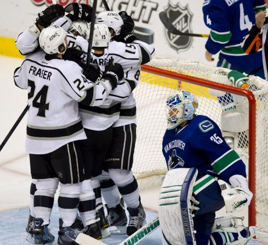The Kings' Brad Richardson is mobbed after eliminating Vancouver with an OT goal.