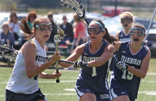 Westwood&#8217;s Kate Rich, who scored 5 goals on the day, was pursued by Framingham&#8217;s Julia Reedy and Hannah Burton during Westwood&#8217;s 15-8 victory last Friday. After a 25-0-1 mark and the Division 1 state crown last year, Westwood is 5-1.