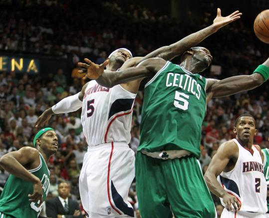 The Celtics' Kevin Garnett beats Hawks forward Josh Smith to a fourth-quarter rebound, shortly before Smith left the game with a knee injury.