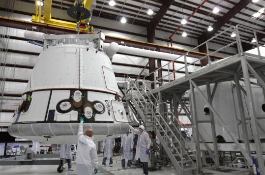 In this NASA photo, the SpaceX Dragon capsule was lifted to be placed atop its cargo ring at Cape Canaveral. The first private run to the International Space Station has been delayed again.