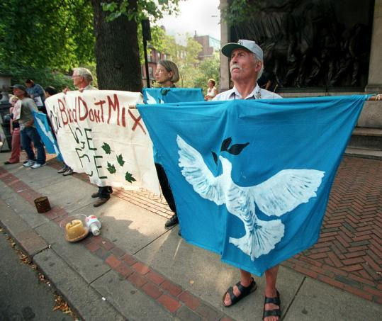 Paul Brailsford, holding a peace flag at the State House in Boston while participating in the one-year anniversary memorial ceremonies of the Sept. 11. terrorist attacks.