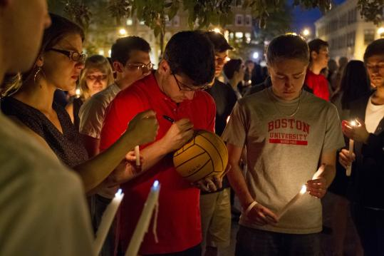 Jeremy Putz signed a water polo ball in honor of teammate Austin Brashears at a BU vigil Saturday night.