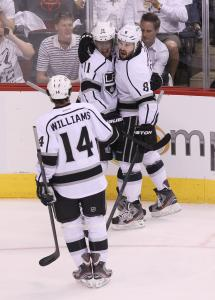 The Kings&#8217; Justin Williams and Drew Doughty (8) greet Anze Kopitar after his first-period goal in the Western finals opener.