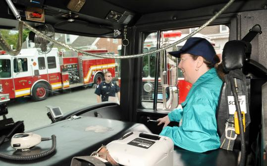 Donna Picone gets a quick ride on a North Reading firetruck after walking to the main station from her Danvers home last week.