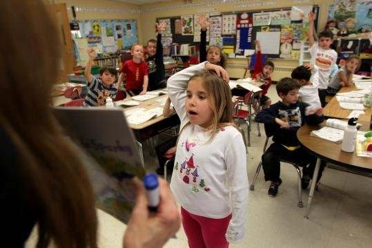 Millis teacher Adria Osborne Cohen signals her first-graders to let Jack Catalano reach an answer in peace.