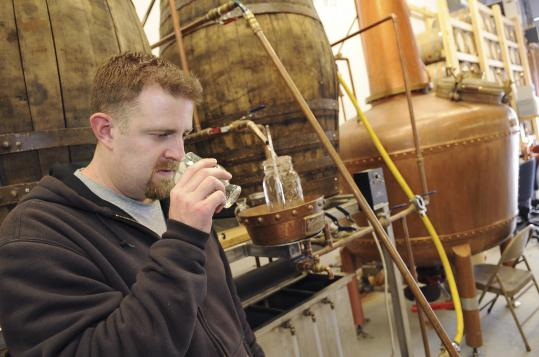 Owner Mathew Perry sniffs a sample of the rum made at Turkey Shore Distilleries in Ipswich.