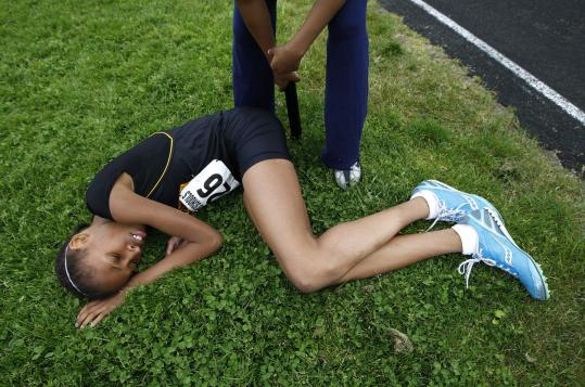Latin Academy's Britney Firmin collapses after anchoring the 4 x 400 relay team to victory.