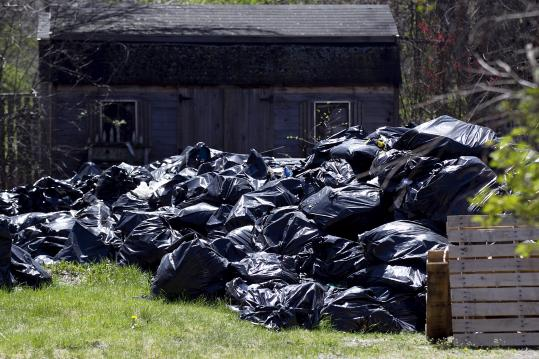 Neighbors have filed complaints over the mounds of garbage bags outside this Osgood Street house in Andover. Health officials have ordered the home's owner to clean up the property.