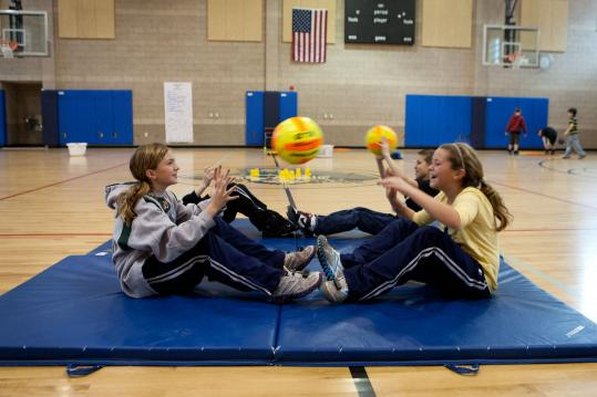 Lauren Anastos (left) and Jaclyn Diemer, both 11, throw a ball in a sit-up position during the morning gym class at Lillian M. Jacobs Elementary School in Hull.