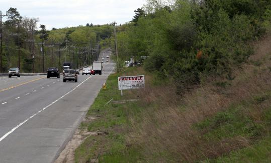 Wrentham officials hope proposed zoning changes will attract more commercial interest in undeveloped land along Route 1. An abandoned property (left) on Wrentham's northern stretch of Route 1 stands in stark contrast to the Patriots Place complex next to Gillette Stadium in Foxborough.