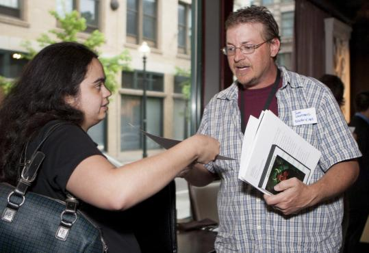 Animator Michelle Bartlett, 24, of Norton handed her resume to John Lindemuth, director of art for Turbine Inc., at a job fair for video game developers in Providence last week.