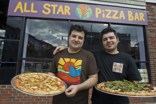 All Star Pizza Bar owners Kosta (left) and Johnny Diamantopoulos with a pair of their specialty pizzas.