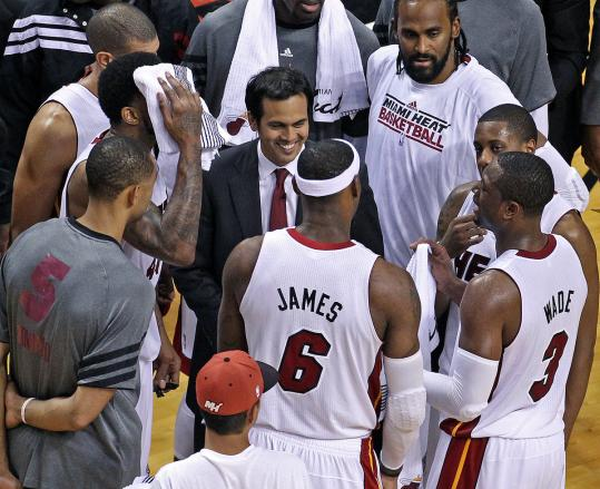 Coach Erik Spoelstra (center) was a happy guy as he huddled with his Heat players late in OT, close to wrapping up Game 2.