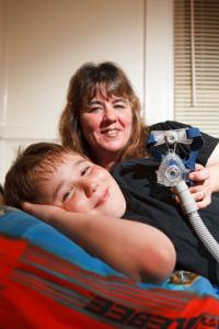 Justin Colamaria with his mom, Tina Foye, and his breathing machine that helps his sleep apnea.