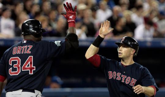 Daniel Nava is congratulated by David Ortiz after scoring against the Blue Jays in the Red Sox' 7-2 victory in Toronto. Nava went 4 for 5 and scored three runs.