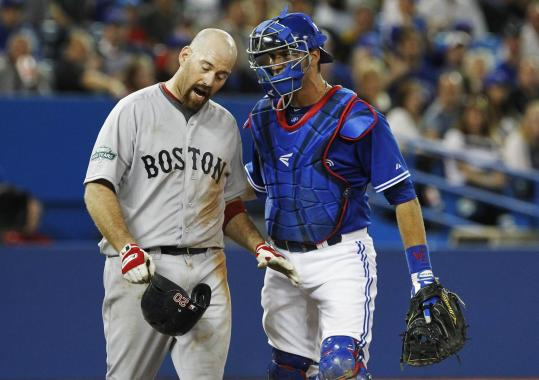Kevin Youkilis is held back by J.P. Arencibia after he was hit by a pitch in the sixth.