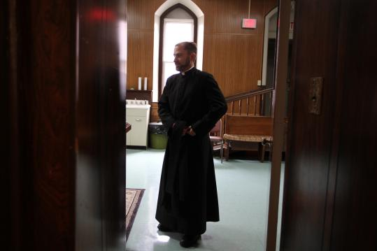 The Rev. Jason Worthley, shown at St. Joseph Church in Somerville, has responsibilities in three parishes in the city.