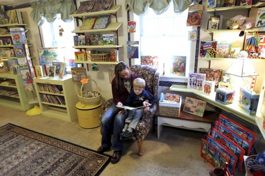 Hamilton resident Merry Kaulbach and her son, Jonathan, sample a book at the Banbury Cross shop in Wenham.