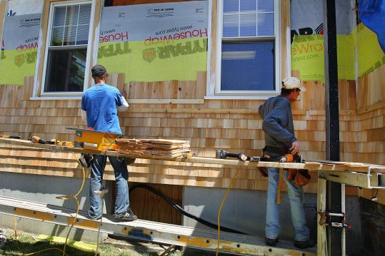 Carpenter Dan Savage of B&N Development installs white cedar shingles on Newbury Town Hall. Volunteers are helping the town save money on repairs.
