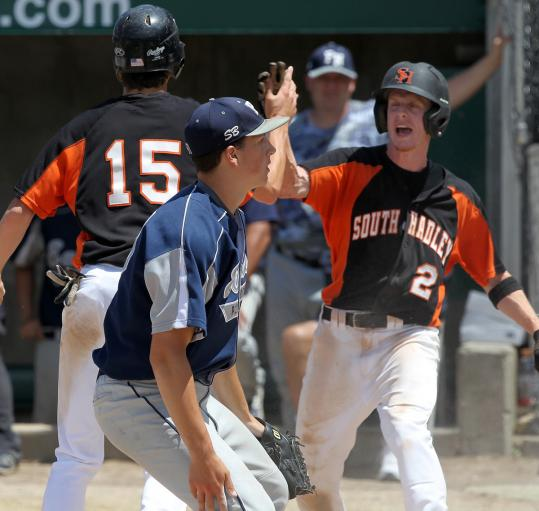 South Hadley's Connor Sheridan (right) is greeted by teammate Nick Robert after scoring the Tigers' first run in the first inning.