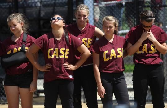 Members of the Case softball team (left) look on with disappointment as Turners Falls celebrates its second title.