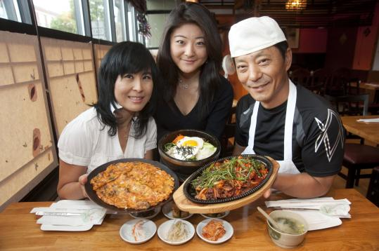 From left: SungAe Choe, daughter InAe Choe, and husband and chef SungJo Choe serve a kimchi seafood pancake, okdol bibimbap, and soon dae bokum, along with an array of side dishes.