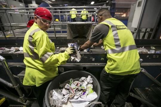 Workers sorted through materials at Casella Waste Systems. Boston is rolling out new programs to boost recycling.