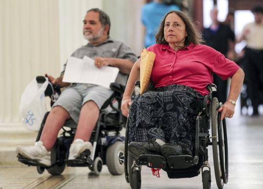 Brian Shea of Somerville and Karen Schneiderman of Jamaica Plain were at the State House Monday to protest fare hikes for The Ride. serving those with disabilities.