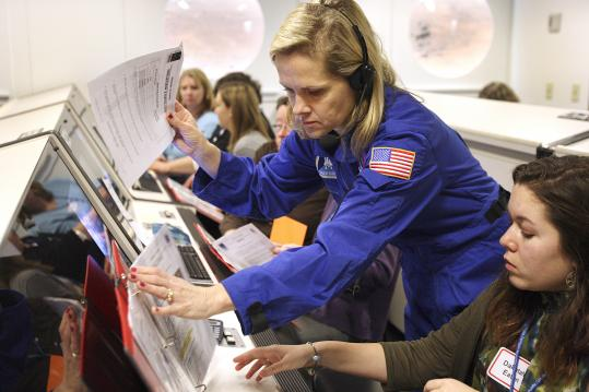 McAuliffe Center flight director Elsa Oberg (center) assists Athol teacher Dakotah Eaton during a 2010 training session.