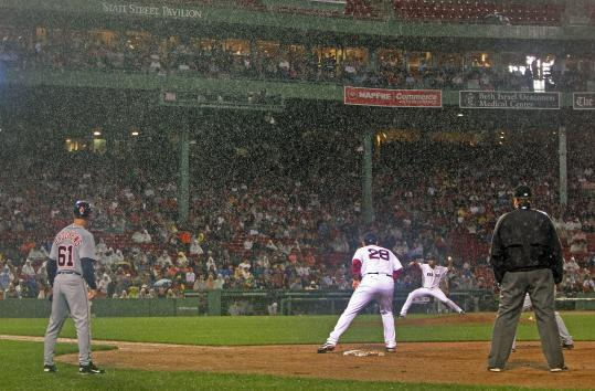 As the rain falls heavily, Red Sox pitcher Franklin Morales fires a pitch in the top of the sixth inning, just before play was halted and the game went into a delay.